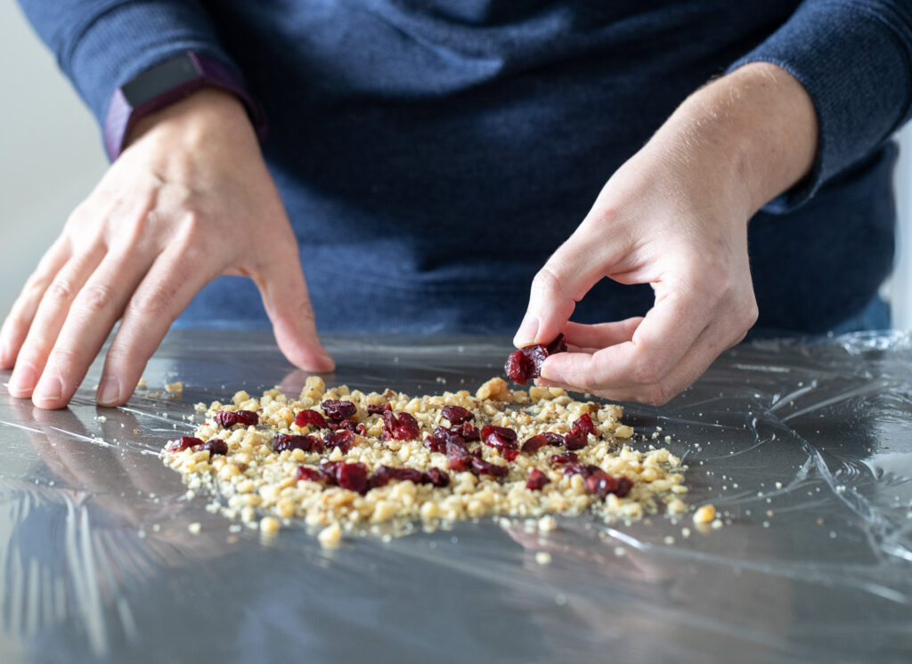 woman adding walnuts and dried cranberries to a piece of saran wrap.