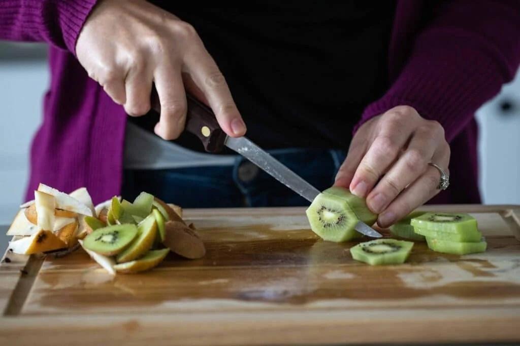 Woman cutting kiwi on a wooden cutting board.