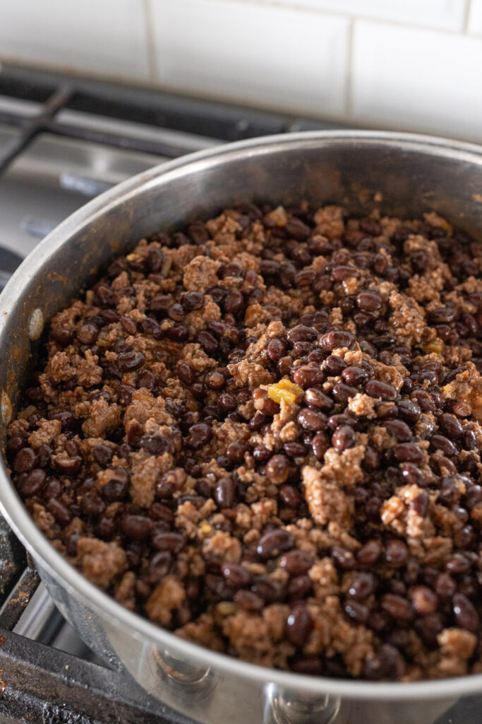 Taco meat and black beans cooking in a pan on the stovetop.
