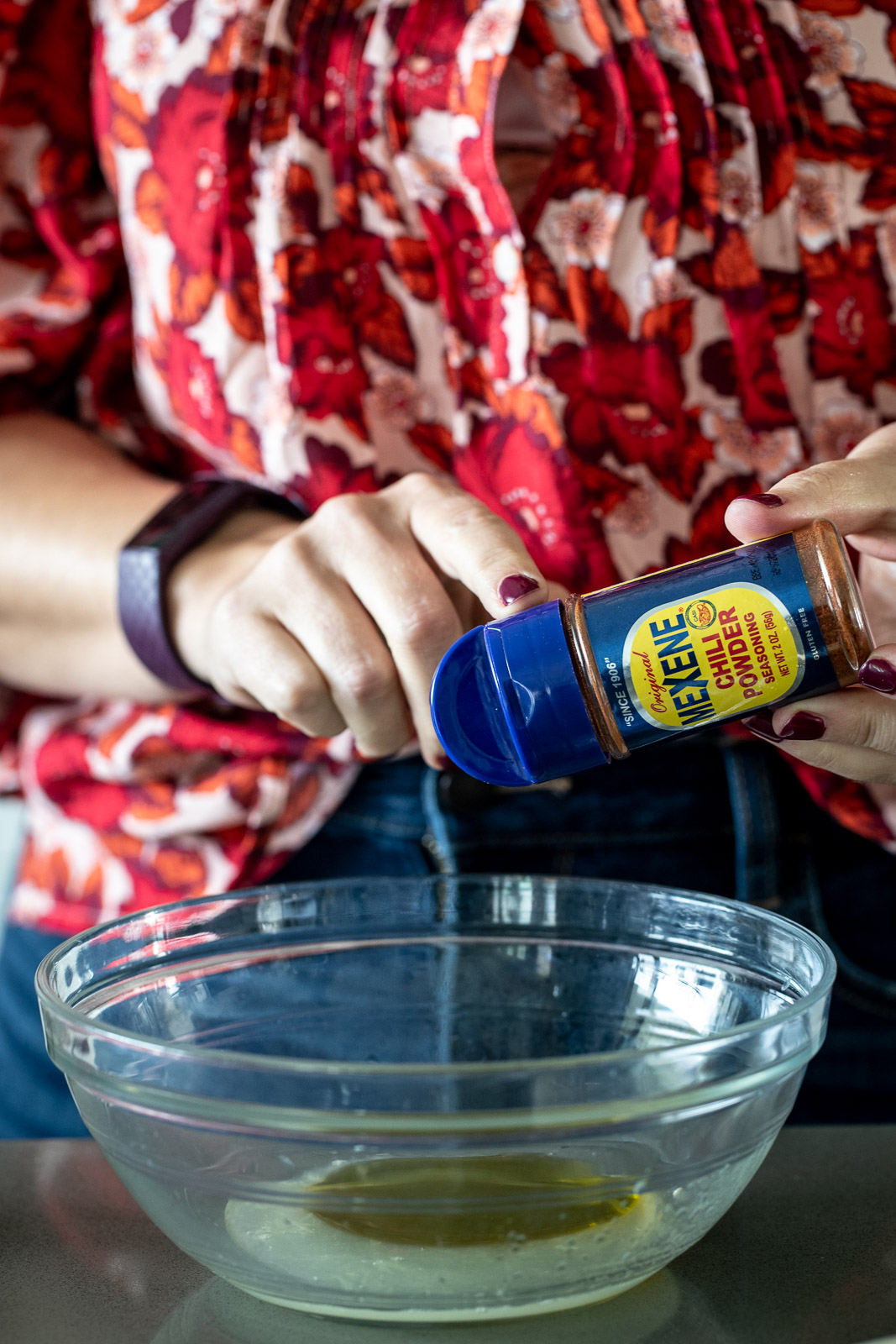 Woman adding chili powder to a marinade in a glass bowl.