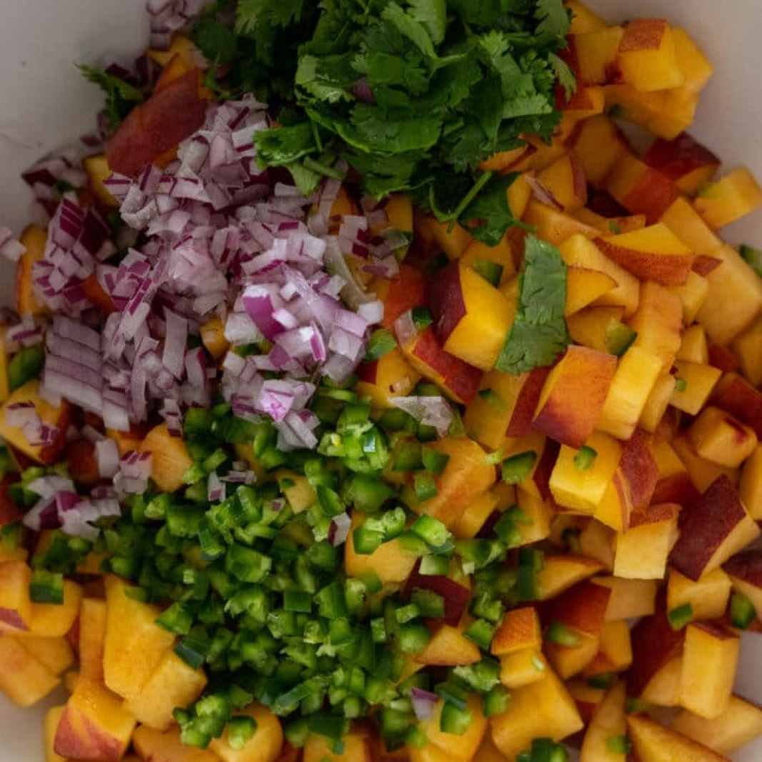 Ingredients for peach jalapeno salsa in a white bowl.