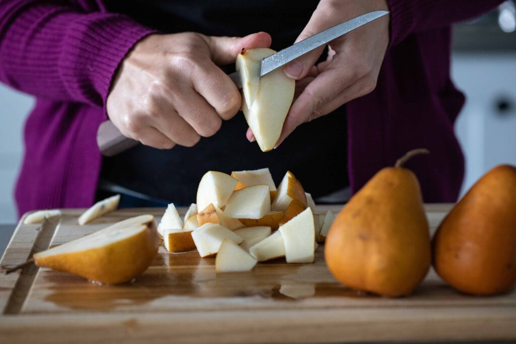 Woman cutting pears on a wooden cutting board.