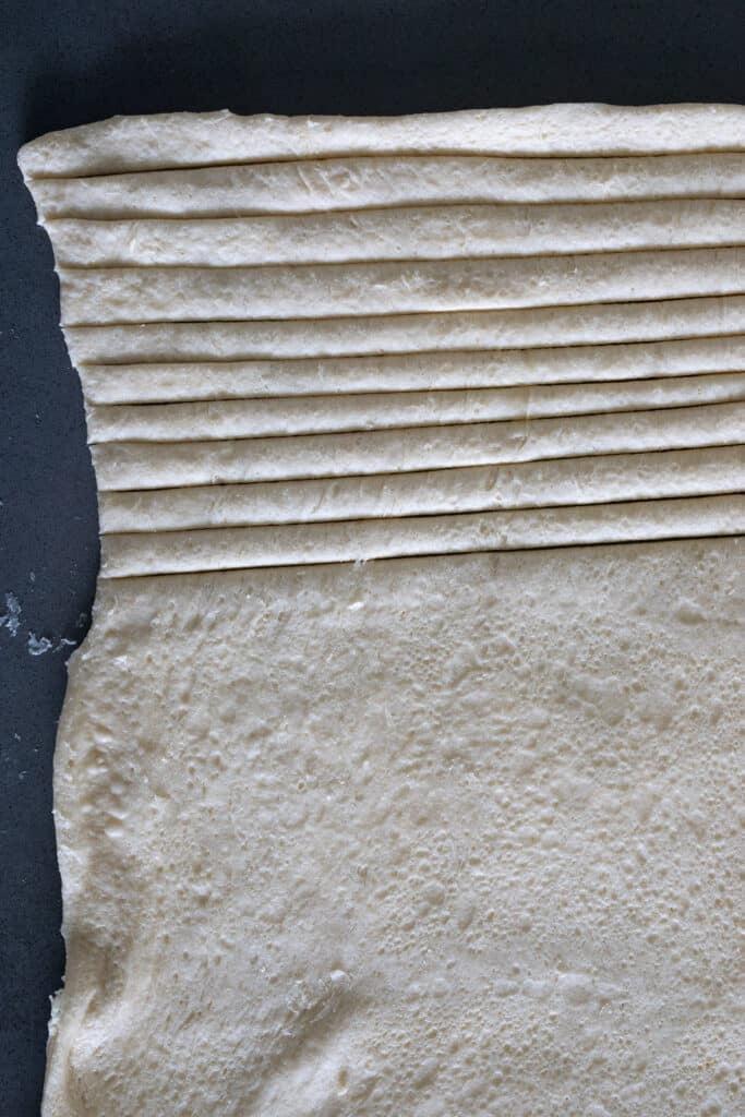 Crescent dough cut into strips on a countertop.