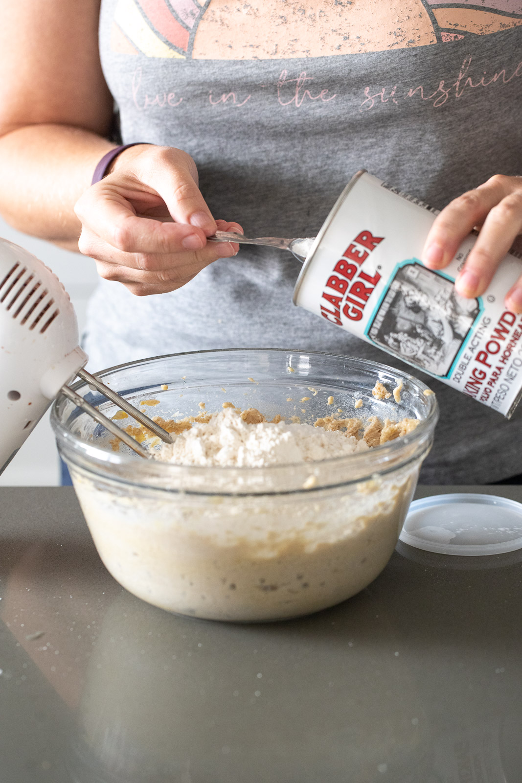 woman adding baking powder to a glass bowl for mixing.