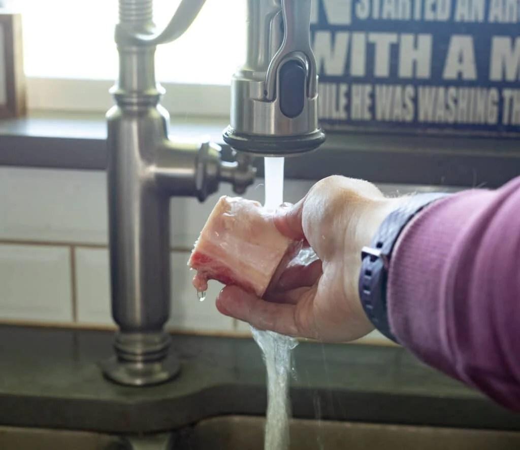 Woman rinsing beef bones.