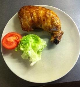 en stor kycklingklubba på en tallrik med sallad