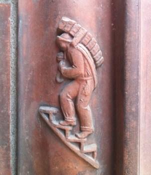 Figur i teglet på Kungsgatan vid Kungstornet. Tegelbärare. Fika och idiot vid övergångsställe
