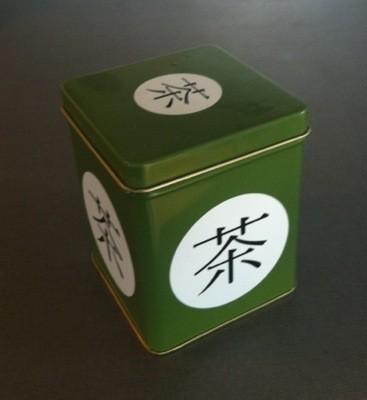 Grön plåtburk med kinesiska tecken