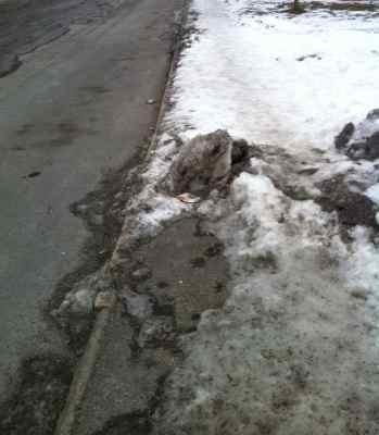 Trottoar och gata med snö och is