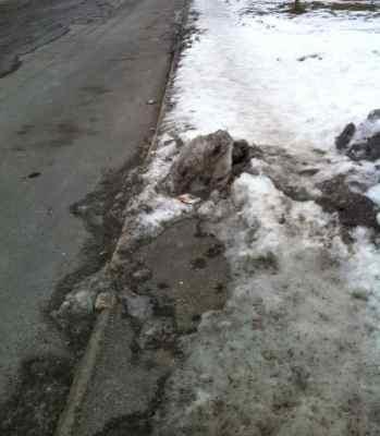 Trottoar och gata med snö och is. Omöjligt att ta sig fram.