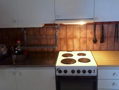 Kök med mörkbrunt kakel, spis
