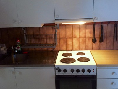 Kök med mörkbrunt kakel och trasigt lysrör.