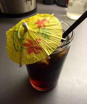Rom och cola med paraply och sugrör. Giftiga drinkar.