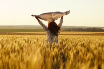 Happy woman with a scarf in the evening field