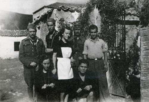 Με την λευκή ποδιά η συγγραφ�ας στην είσοδο του Πατρικού της σπιτιού στα Δίδυμα περίπου το 1943. Φωτογραφία από το βιβλίο, Γιόνα Μικ� Παϊδούση, « Ο Κόκκινος Επιτάφιος », Εκδόσεις Βιβλιόραμα, Αθήνα 2008.