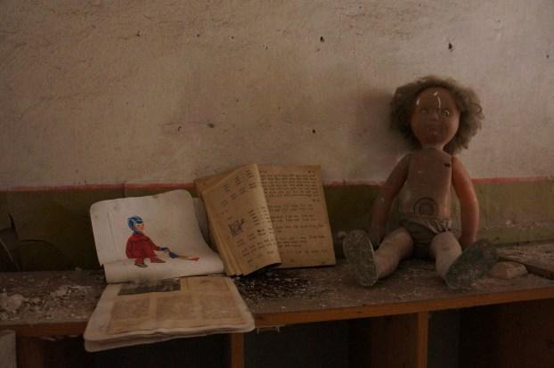Bøker og ei dokke i ein forlatt barnehage i Tsjernobyl.