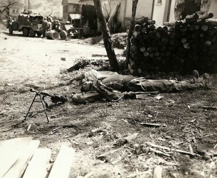 A German machine gunner shot through the head, laying next to his smashed gun. Germany.