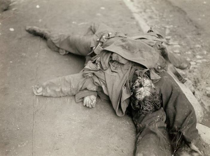 Bodies of German soldiers on top of each other lying in the street gutter, France. The horrors of war.