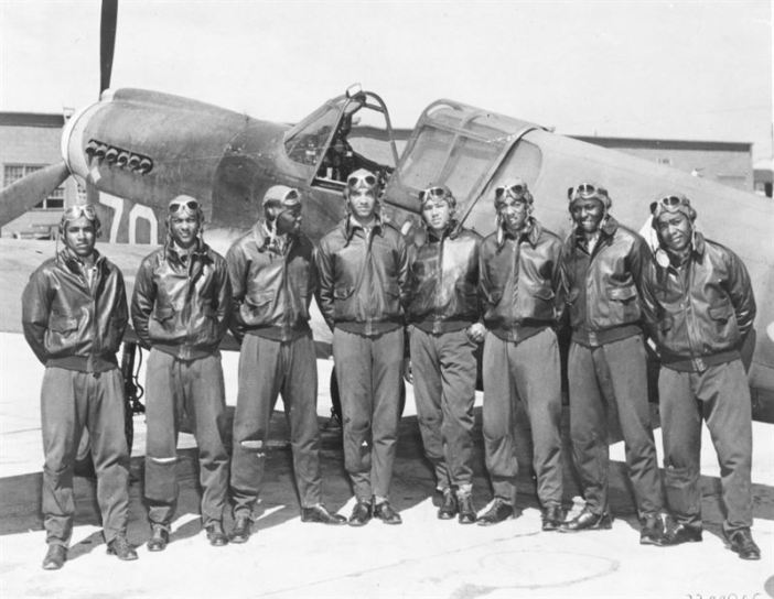 Eight Tuskegee Airmen in front of a P-40 fighter aircraft. (Credits: US Air Force)
