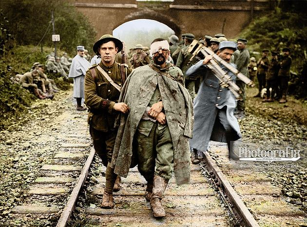 A British soldier helps a wounded German prisoner walk along a railway track.