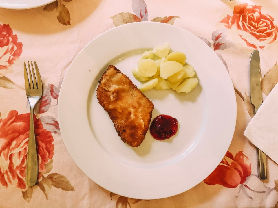 chicken schnitzel on a plate with potato salad and lingonberry sauce