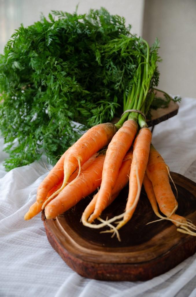 cenouras com a rama sobre tábua redonda de madeira