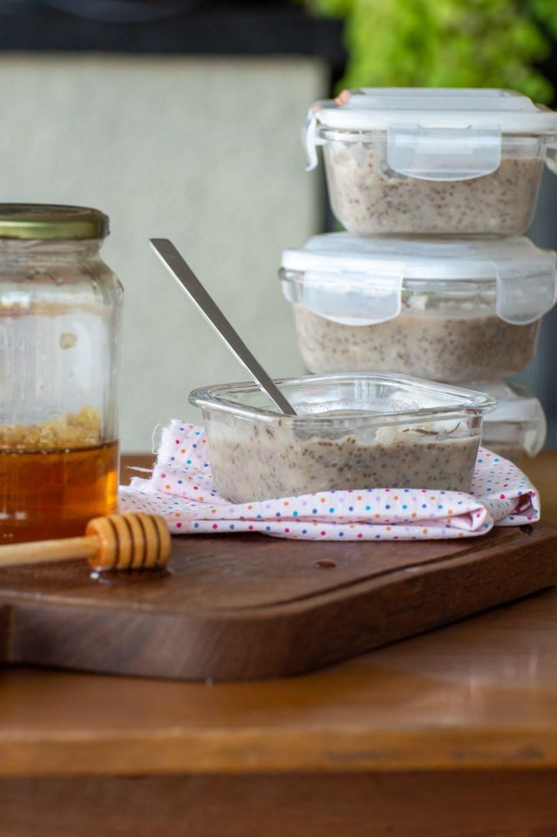 Pudim de banana e chia empilhados um atras do outro e um aberto ao lado de um pote de mel