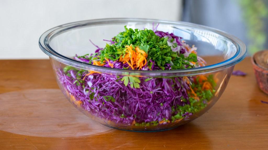 tigela transparente com os ingredientes da salada de repolho roxo super coloridos