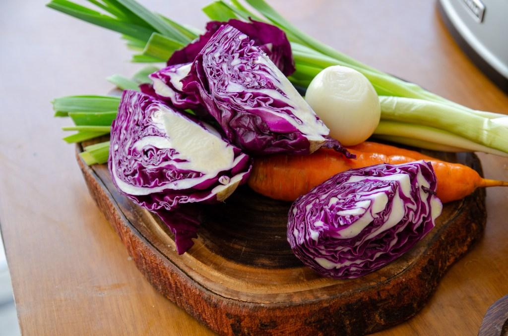ingredientes da salada de repolho roxo sobre uma tábua de madeira