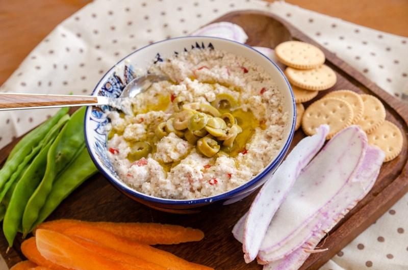 ricota vegana em um pote transparente servida com vegetais