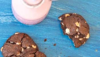 cookies de chocolate sobre mesa azul acompanhado de um copo de vitamina de morango