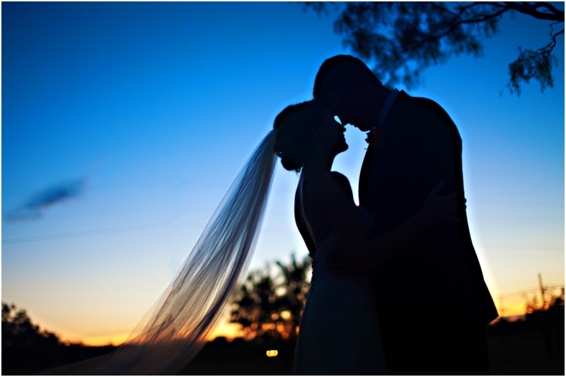 Beautiful wedding day silhouette of bride and groom at sunset during the reception