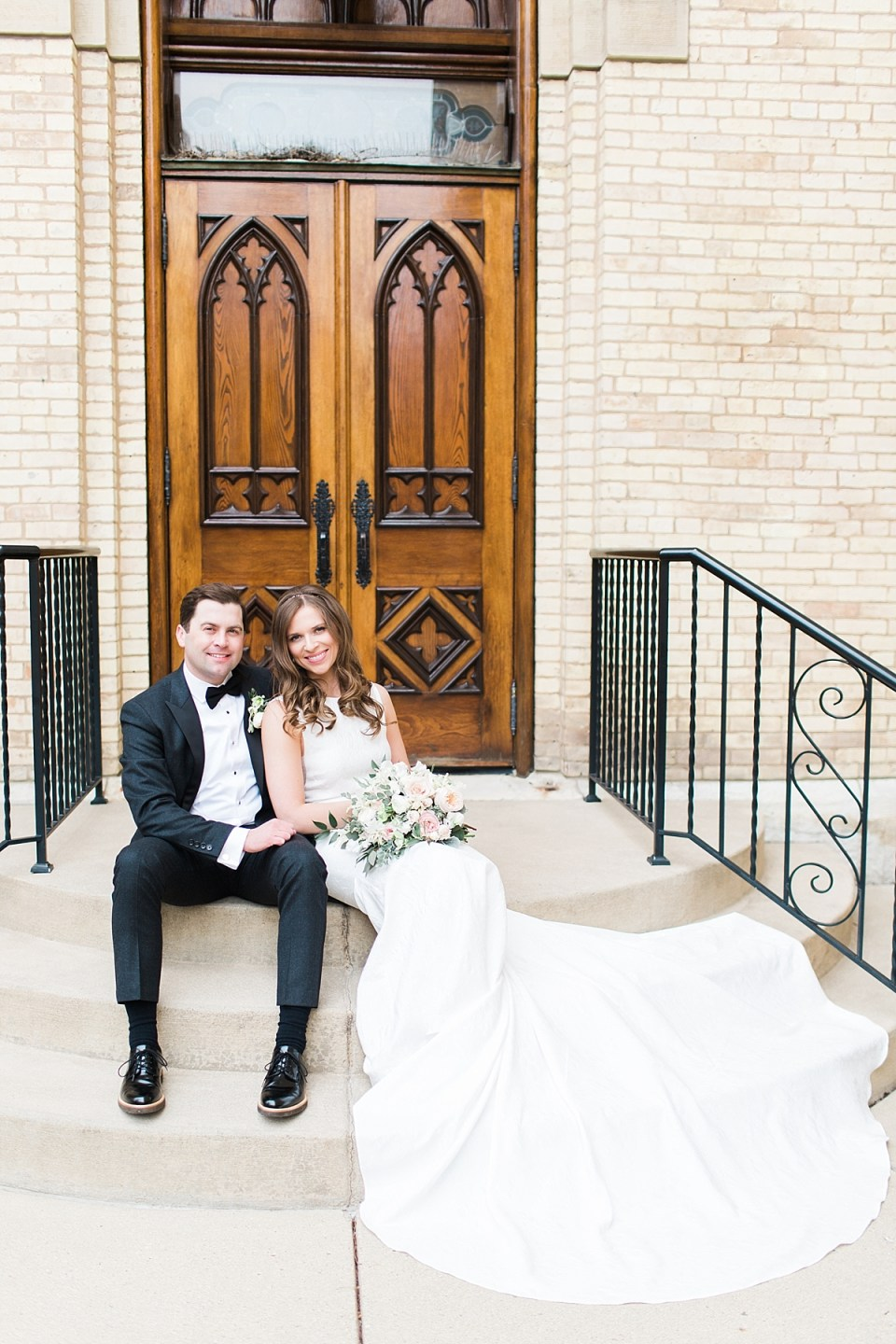 Arielle Peters Photography | Bride and groom sitting in front of cathedral doors on wedding day at the Basilica of the Sacred Heart in Notre Dame, Indiana.