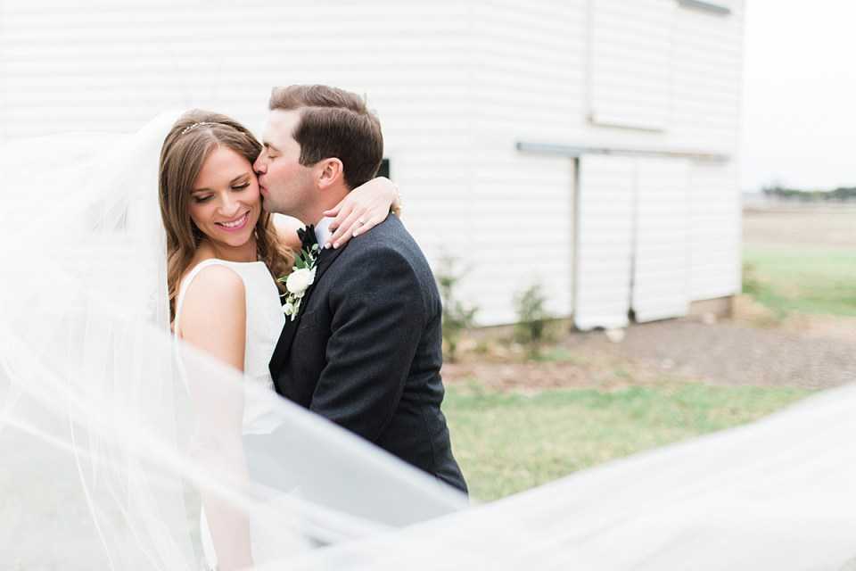 Arielle Peters Photography | Bride and groom kissing in front of barn on wedding day at St. Joseph's Farm in Granger, Indiana.