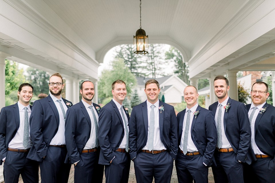 Arielle Peters Photography | Groom and groomsmen smiling with hands in pockets outside on wedding day at Sycamore Hills Golf Club in Fort Wayne, Indiana.