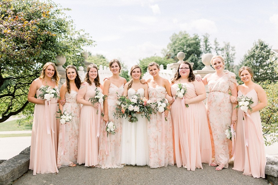 Arielle Peters Photography | Bride and bridesmaids smiling outside with bouquets at The Bridgewater Club in Carmel, Indiana on wedding day.