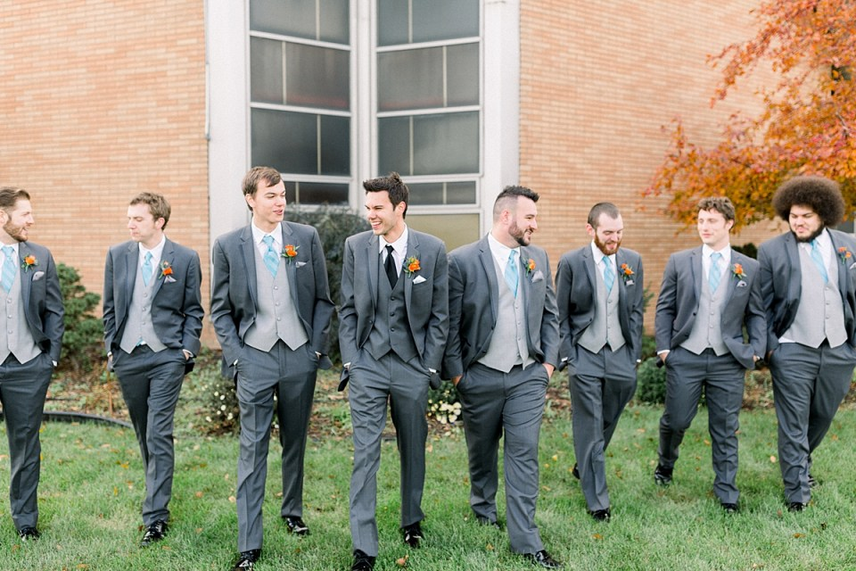 Arielle Peters Photography | Groom and groomsmen walking and smiling outside on fall wedding day.