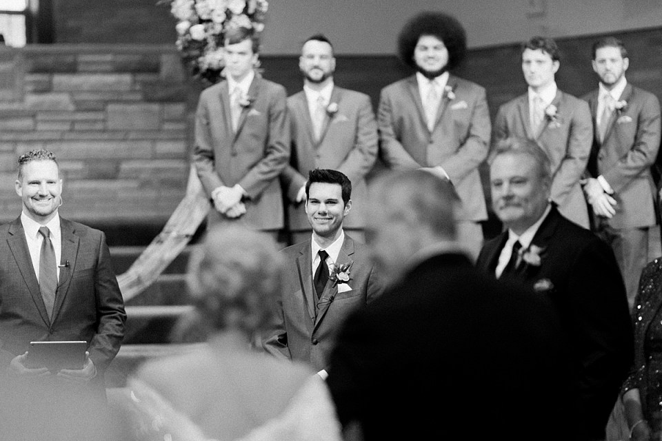 Arielle Peters Photography | Groom smiling at the bride as she walks down the aisle on their fall wedding day.