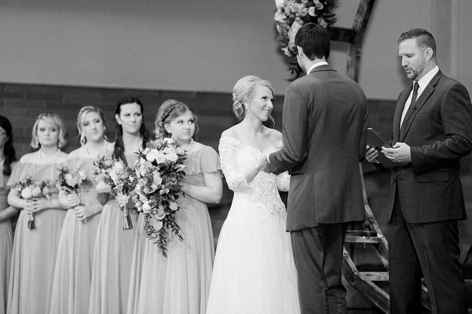 Arielle Peters Photography | Bride and groom smiling and holding hands at the alter on their fall wedding day.