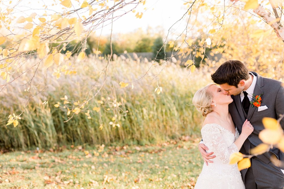 Arielle Peters Photography | Bride and groom kissing in a field next to trees on fall wedding day.
