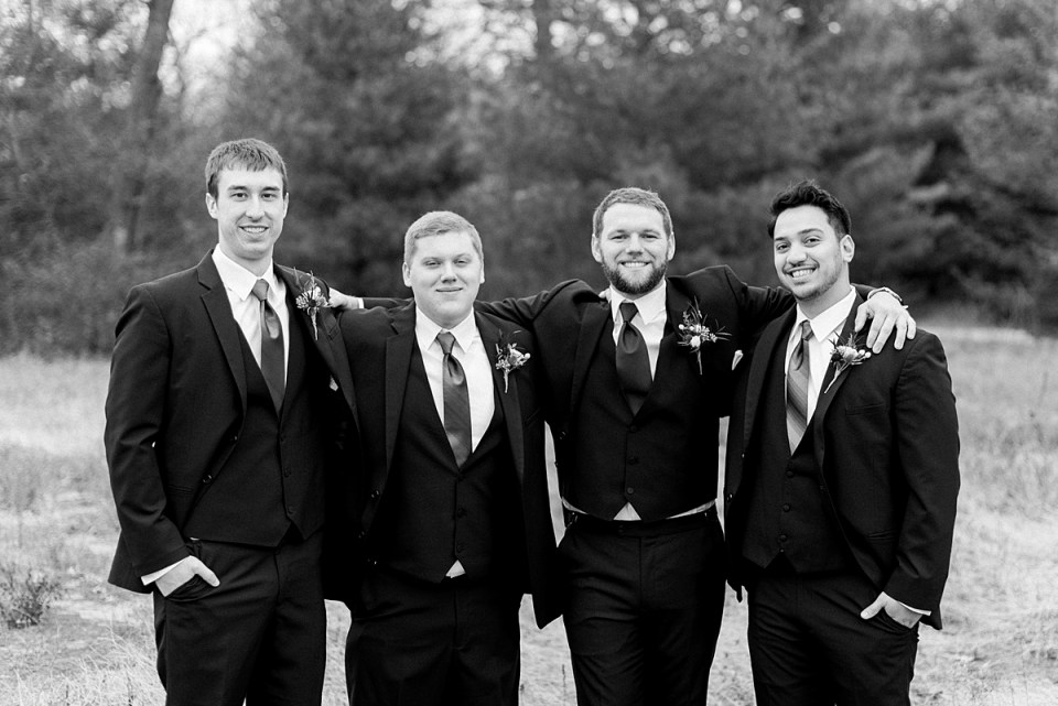 Arielle Peters Photography | Groom and groomsmen smiling in field on wedding day.