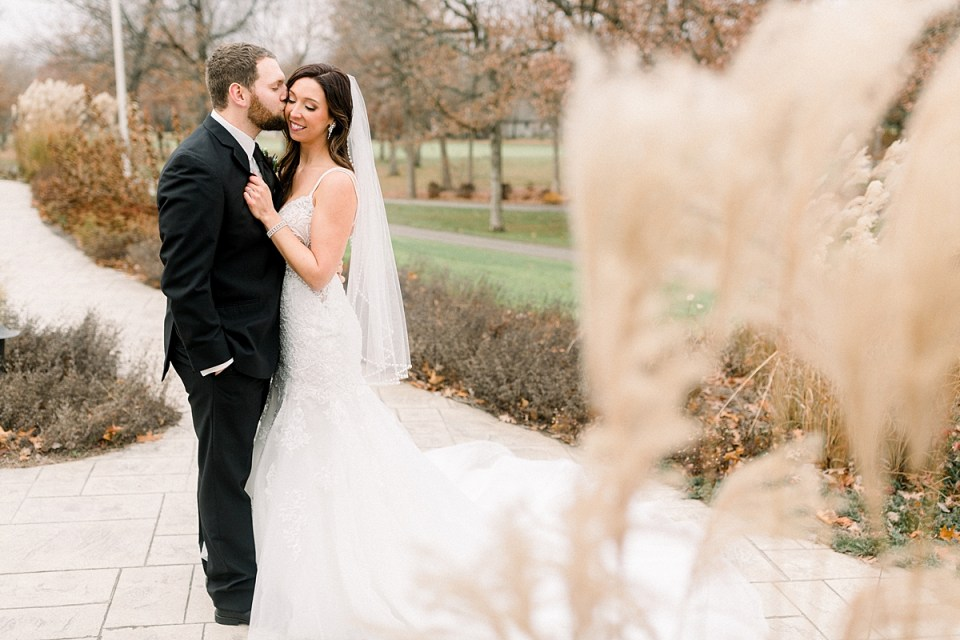 Arielle Peters Photography | Bride and Groom kissing at golf course on wedding day.