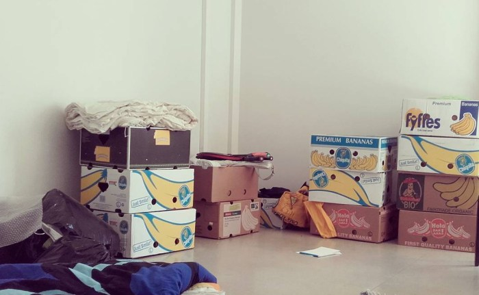 How to save money for traveling? Chiquita boxes used for storage in an empty apartment before moving out.