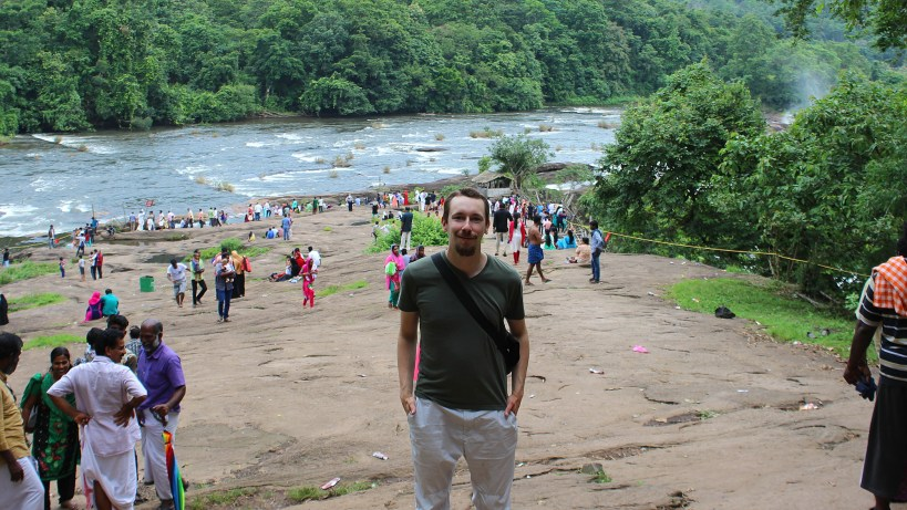 Monsoon travel in Kerala. Crowd of tourists above the Athirappilly Falls in Kerala.