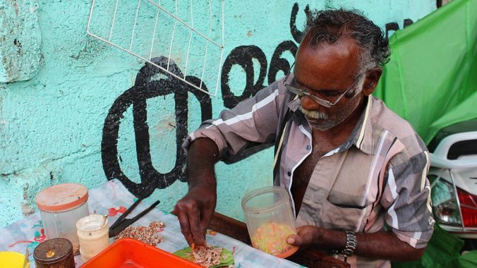 A vendor making paan (chewable tobacco) in Kerala, India.