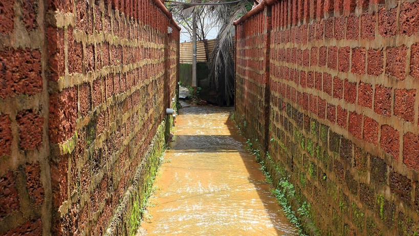 A small path with flowing water between two red brick walls.