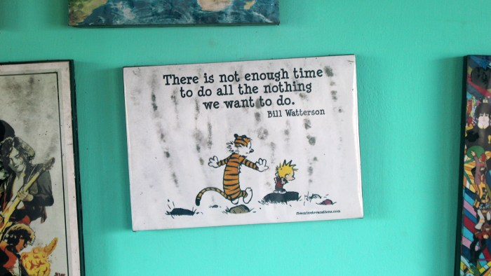 "A Calvin & Hobbes print at the wall of the hostel Zostel Gokarna's with the quote ""There is not enough time to do all the nothing we want to do."" by Bill Watterson above the characters."