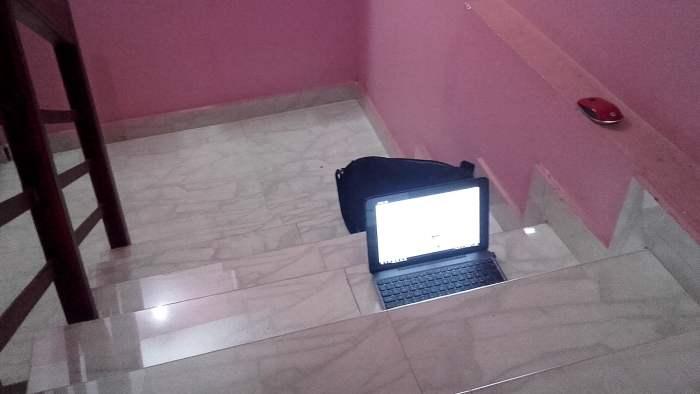 A laptop on a dark hotel stairway.