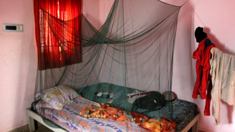 Backpackers accommodation A simple bed in a guesthouse bungalow with an installed mosquito net and laundry hanging from a travel clothesline.