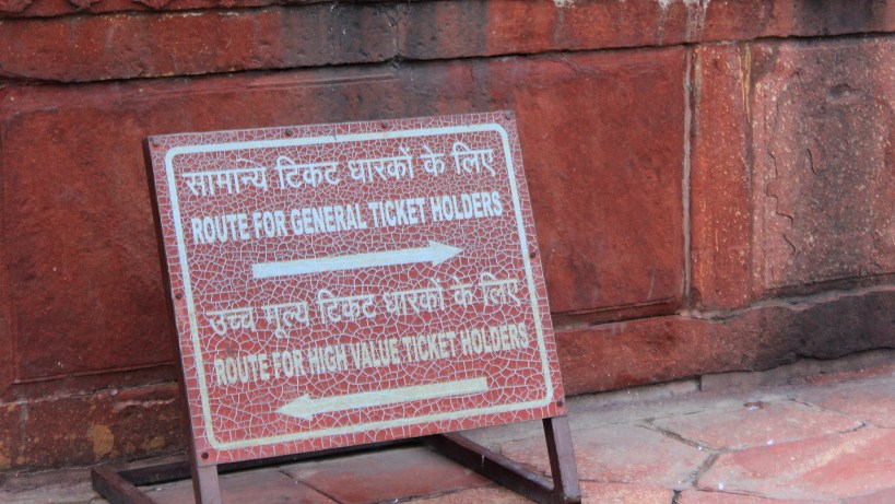 A red signs showing different routes for general ticket holders and high value ticket holders at Taj Mahal, Agra.